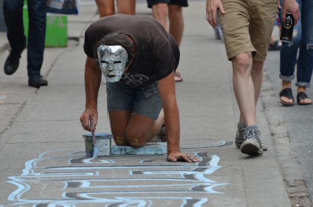 victor painting on the sidewalk in Kensington.  He's wearing a shiny sparkly mask over the top of his head. people are walking past #whatsvictorupto