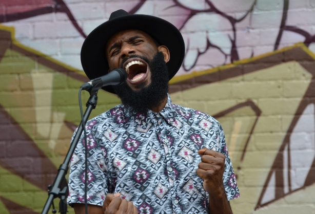 a young black man in black wide brimmed hat sings in front of a microphone, part of a band performing ouside in front of a mural on a wall