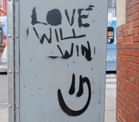on the side of a grey metal box, written in black, with a smiley face under the words, love will win