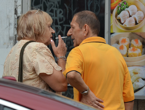 couple, one is smoking, man in yellowish orange shirt, standing by a chinese restaurant, pictures of the food on the wall behind them.