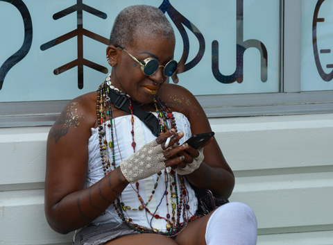 black woman with very short hair, round sunglasses and white top, wearing many strands of beads, sitting on a bench on her phone