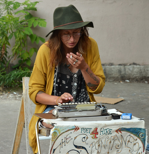 woman with green felt hat with floppy brim, smoking a cigarette, sitting at a small table and typing on an old Smith Corona typewriter.  She has a sign on the table that says, poet for hite, the spontaneous poet.