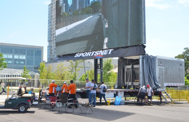large TV screen mounted on a metal post outside the back of a truck, mobile TV network setup to cover the Indy. picture on screen is of part of the racetrack.