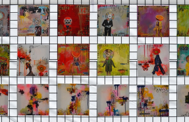 square artworks arranged in a grid on a metal mesh wall, hanging at an outdoor art fair.