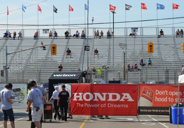 view of the stands for watching Honda Indy in Toronto, with flags flying from the top row, but not too many people in the stands because it's early in the day