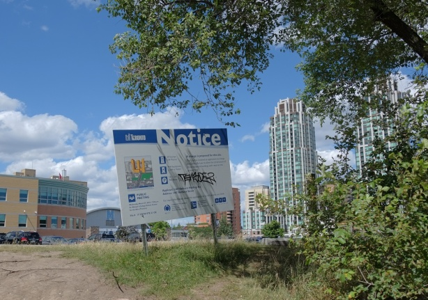 blue and white city of Toronto development notice sign on a small hill, by some trees, in front of a vacant lot. Highrises in the background