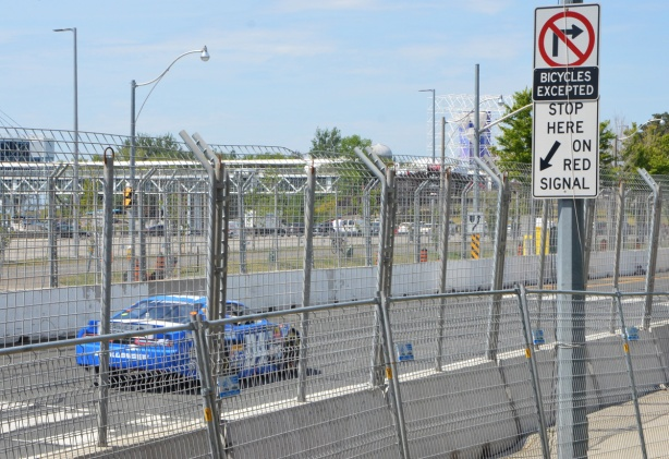 a blue car races on track with is along Lakeshore, behind two layers of chainlink fence