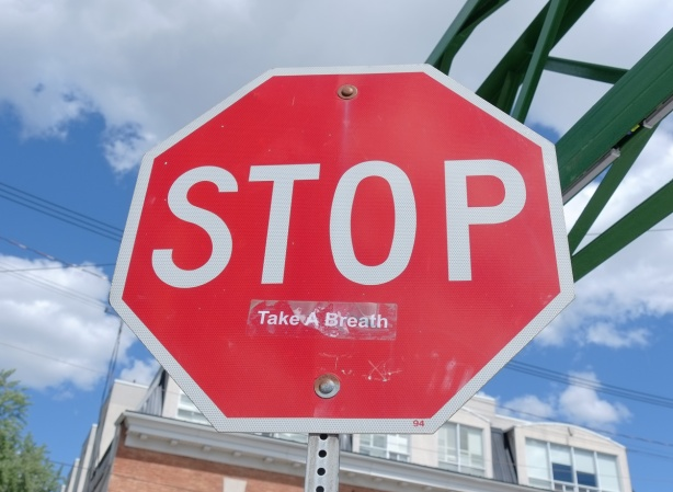 red octagonal stop sign with a sticker on it that says take a breath