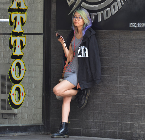 a woman standa against an exterior wall, beside a tottoo place. The word tattoo is in large yellow letters beside her, her hair is multicoloured, she is wearing a short dress, knee bent with one foot against the wall, phone in hand, black jacket over her shoulders