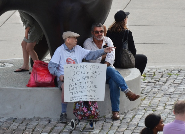 people sitting by the Archer, a Henry Moore sculpture, at Nathan Phillips Square. An older man is talking to another man. He is holding a hand written sign that says Thanks to Doug Ford