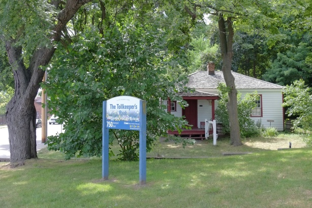 The Tollkeeper's Park, sign, green space, trees, and an old small wood frame house, now a museum,