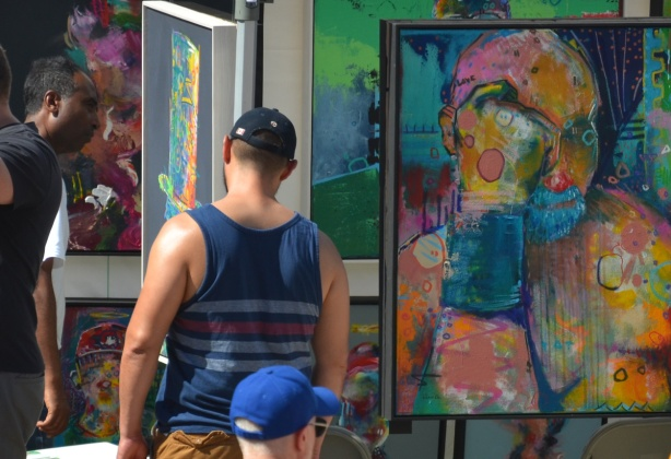 three men looking at paintings, Nathan Phillips Square, outdoor art fair