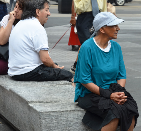 three people sitting on a concrete bench outdoors at Yonge Dundas Square. An older woman with teal long sleeeved shirt and light blue hat, a man in a white t-shirt with black moustache, with a woman leaning against his shoulder with her eyes closed