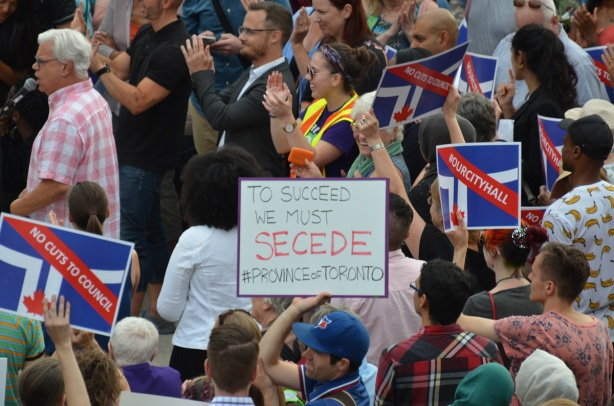 Crowd of people at protest rally at city hall in Toronto. One man holds a sign that says to succeed we need to secede