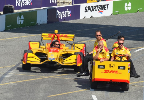 four men on a cart tow a yellow yellow race car covered with DHL ads into place before the start of a race