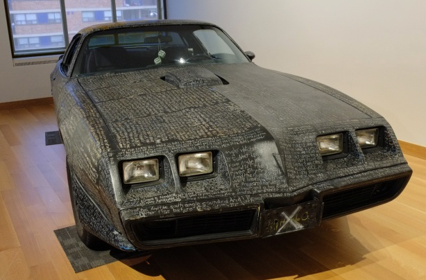 a 1980 Pontiac firebird trans am, painted in black house paint and then words scratched into it, the words from Revelations in the New Testament of the bible, every part of the black surface is covered with words, in an art gallery