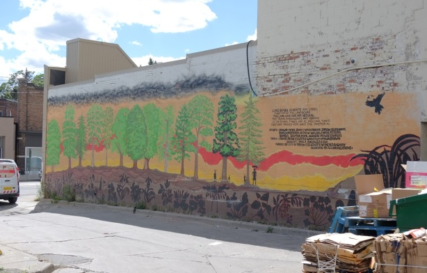 mural in a laneway, painting of many trees with red and yellow sky, dark brown earth, and a few small black figures, some words beside it