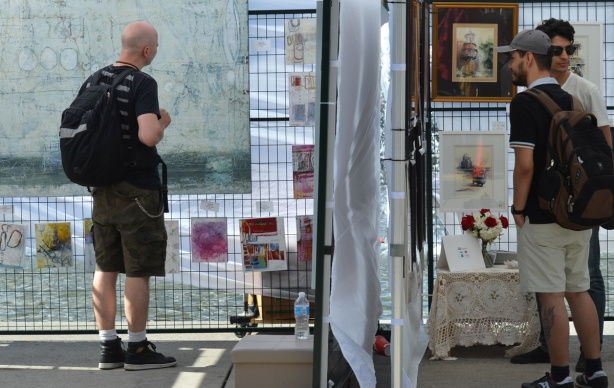 three men, in two different booths, side by side, looking at paintings, Nathan Phillips Square, outdoor art fair