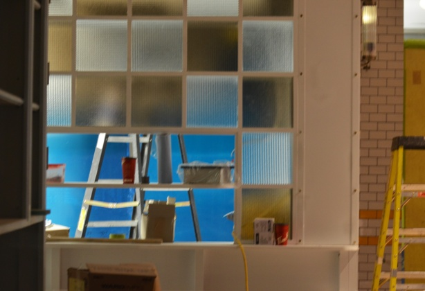looking in the window of a construction site, two ladders, square panes of interior glass on a wall
