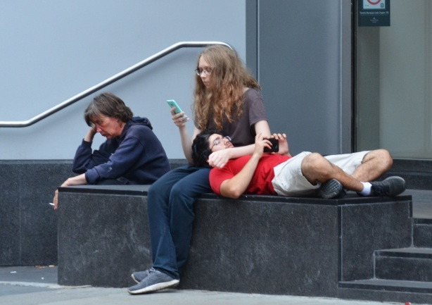 three people, two sitting, one smoking and the other on her phone. The third person is male, lying down with head on lap of woman on her phone, outside,