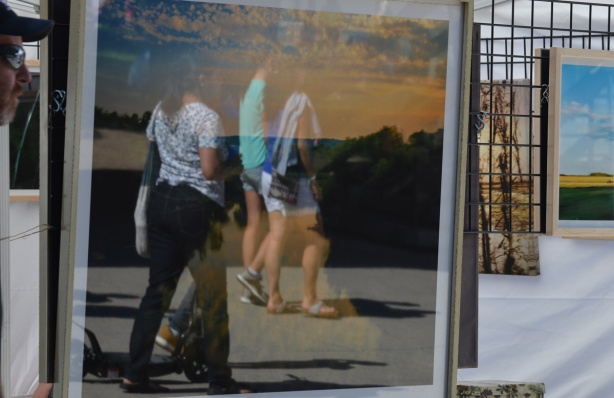 reflections in a framed artwork, people passing by, outdoor art fair
