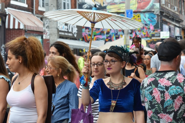 woman in short velvet close fitting top, large necklace, and holding a white parasol walks down a street in a crowd of people