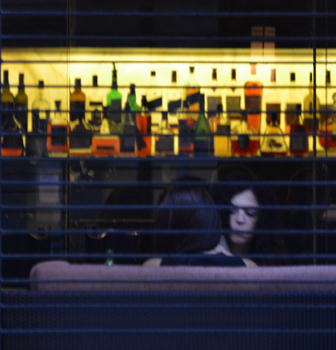 from the outside, looking into a bar. Line of bottles on a back lit shelf, two women takling near the window
