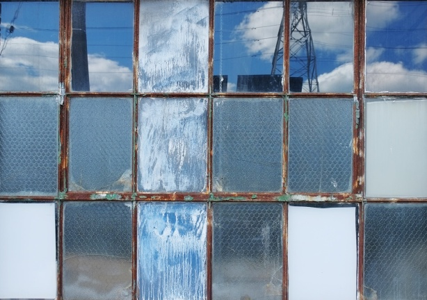 a window consisting of 18 panes of glass, 6 across and 3 down, some have texture and some are clear. the clear ones are reflecting the blue sky and clouds.