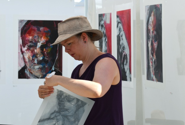 woman in a brown hat starts to pack up her paintings of people's faces at the end of an outdoor art fair in Toronto