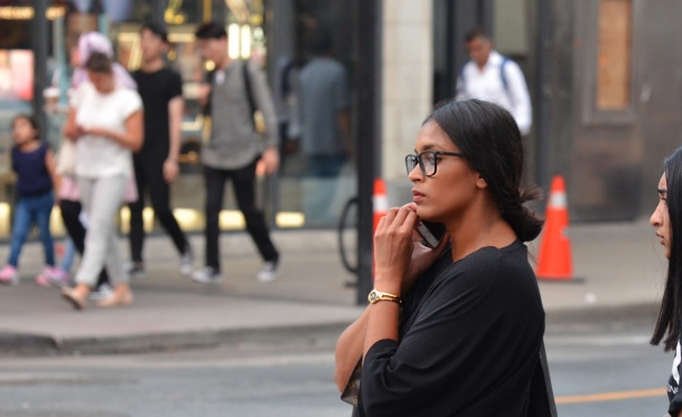 a woman on the sidewalk, with people on the other side of the street in the background