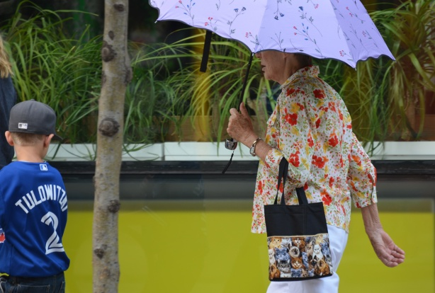 an older woman carrying a pale purple umbrella, and a handbag with pictures of cats on it, a blouse with orange flowers on it