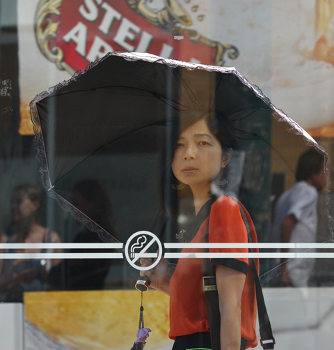young Asian woman under a black umbrella, standing in a TTC bus shelter, reflections off her umbrella of other people, plus a stella artois beer ad