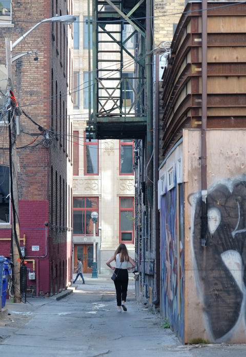 a woman walks down an alley, away from the camera, metal fire escape staircase is above her, brick buildings beside her