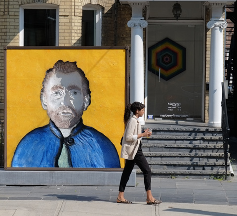large square blue and yellow artwork that looks like the face of Vincent Van Gogh in front of a building with pillars and front steps. A young woman is walking by