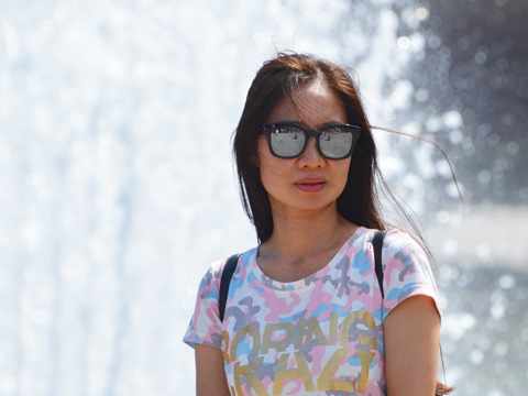 young woman in sunglasses poses in front of a fountain