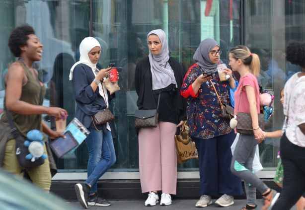women in head scarves standing beside glass window of a store, other women walking past