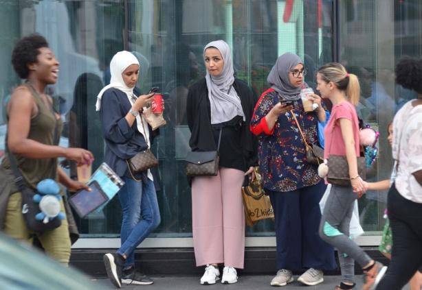 women in head scarves standing beside glass window of a store, other women walking past