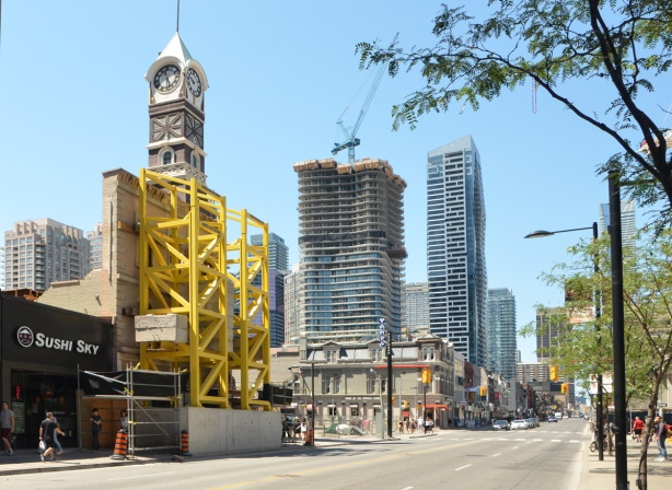 looking north up Yonge Street towards Grosvenor, clock tower still there, yellow scaffolding holding up the facade of an old brick building