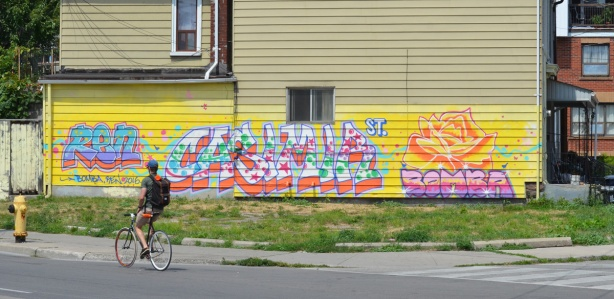 a man cycles past a pale yellow house on Dundas St that has has a bright coloured mural across the bottom of it, text, in blues and pinks