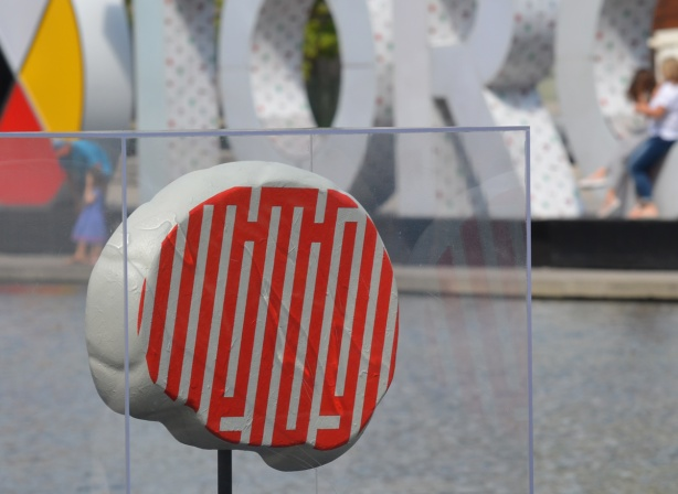 2 dimensional brain, artwork, designed with orange and white lines, beside water at Nathan Phillips Square, 3D toronto sign behind it