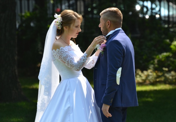 a bride adjusts the groom's collar, long white dress with lacey sleeves and veil tied back on the bride. groom is in a blue suit