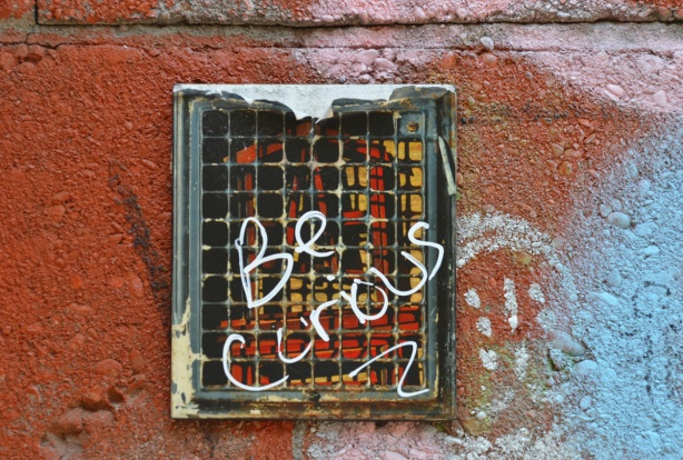 on a graffiti covered wall, a stikman picture with the words be curious written across it in white
