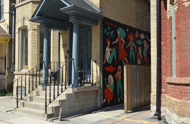 a mural by Emily May Rose of figures of woman on a black background on the side of a building, a fence runs parallel to it, entrance ways to buildings