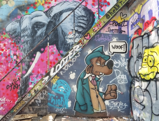graffiti above and below a diagonal metal staircase, an elephant above the stairs and a dog below. The dog is saying woof