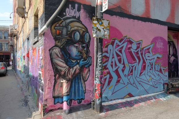 a mural of a person in an old fashioned aviator's helmet and goggles, and wearing a blue dress, on a door in an lane