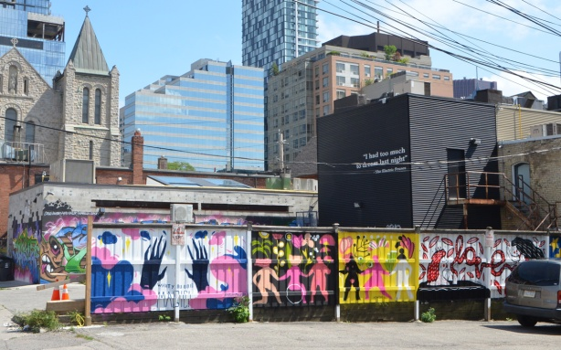 fence with murals painted on it, large buildings behind it,