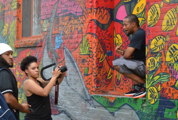 graffiti alley, a group is shooting a music video, black man in on window sill lip synching the words while a woman films