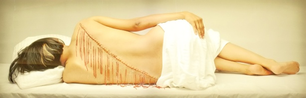 fringe, by Rebecca Belmore, a photo of a woman's back as she's lying down, scar and beads