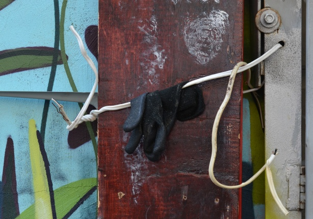 a black glove has been left on some wires by a wall with street art on it