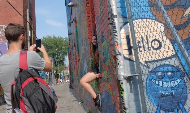 a woman sits on a window sill on a building iin Graffiti Alley as a man takes her picture
